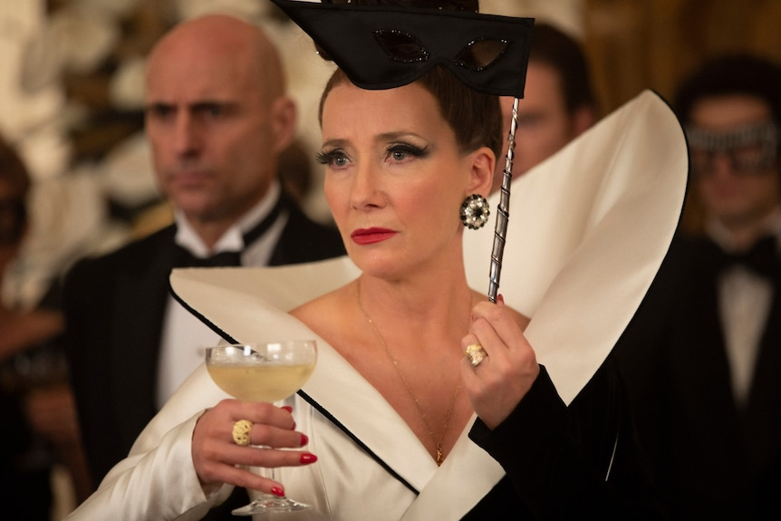 Film still of Emma Thompson as The Baroness wearing a structured dress, holding a martini glass and eye mask in Cruella