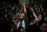 A protester chants while holding a Palestinian flag among a crowd during a demonstration in France.