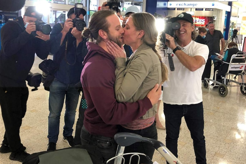 A couple kiss in front of photographers