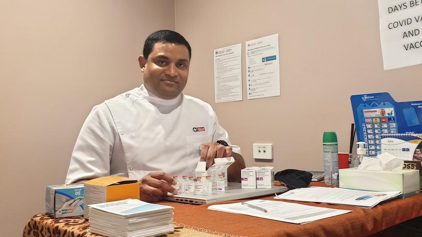 Dorrigo Pharmacist Sri Popuri sitting in front of vaccines
