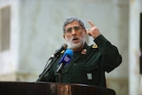 A bearded General Esmail Ghaani in a green uniform gestures as he delivers a speech in 2017.