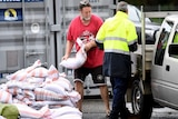 A man loads up sandbags to his car