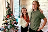 A girl and boy standing inside a home against a brick wall with Christmas tree in the background