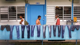 Men walk along a balcony where a row of jeans are being dried in the sun