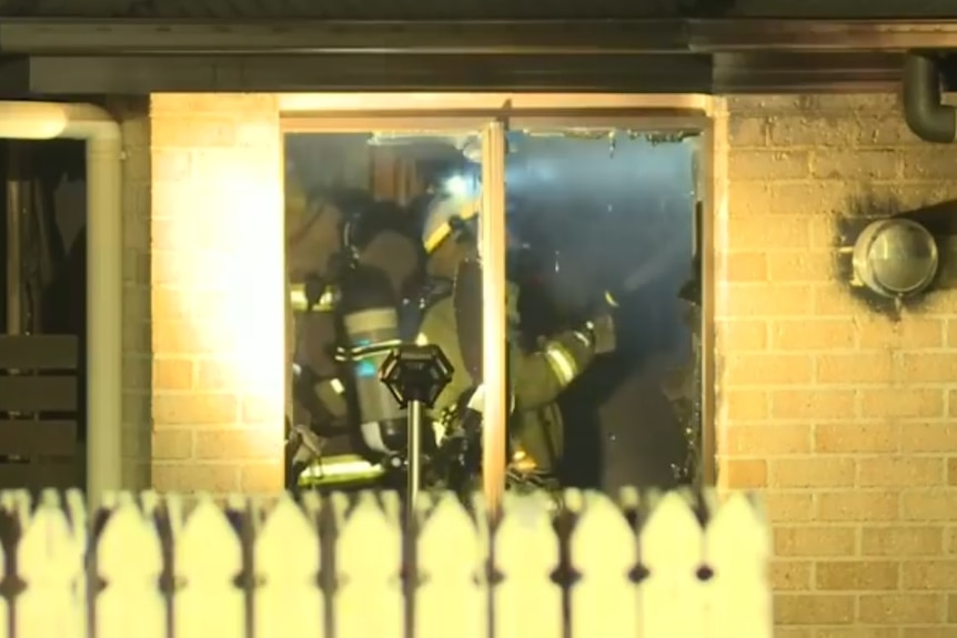 A close up shot through a window as firefighters extinguish a blaze at a Beerwah unit.