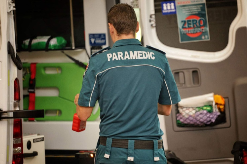 A Queensland paramedic stands at the back of an ambulance.