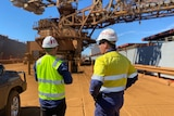 Rio Tinto workers stand talking on the dock at Dampier with loader in front of them and ships to the side.