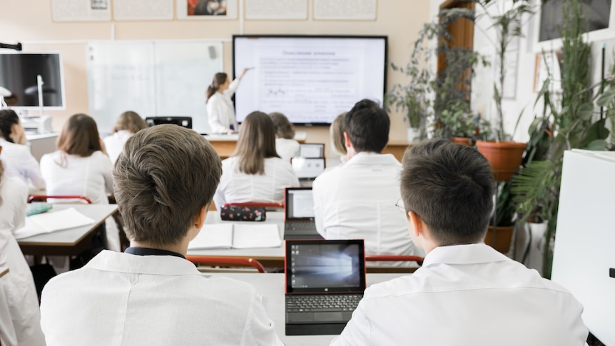Rows of students wearing collared uniforms and using small laptops at their desks, while a teacher points to a whiteboard.