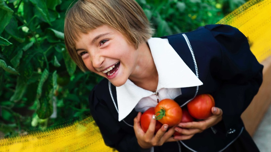 A young child smiles in a garden holding homegrown tomatoes she has harvested, easy veggies to grow with kids.