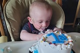 Baby with breathing tubes in his nose blowing out candles on his first birthday cake.