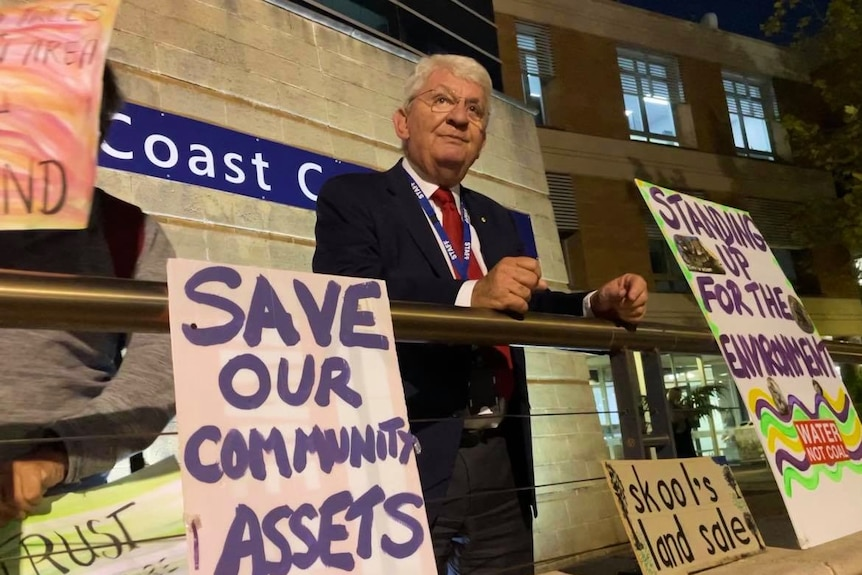 A man in a dark suit looks out at crowd, surrounded by signs some read save our community assets