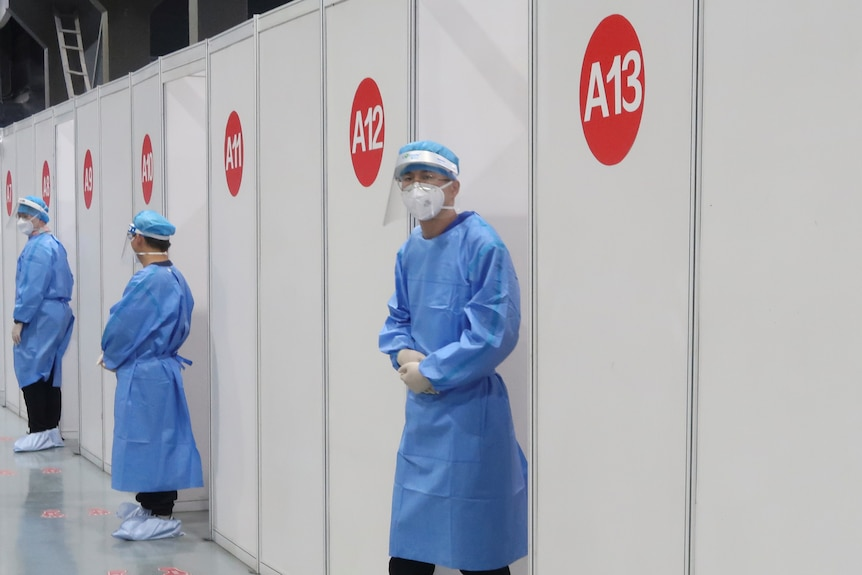 Staff members wait outside booths at a vaccination center in Beijing.