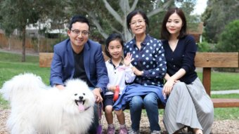 Sean Dong, his wife, mother and young daughter sit on a park bench smiling with their fluffy white dog