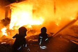 Two firefighters silhouetted against flames that have engulfed a building