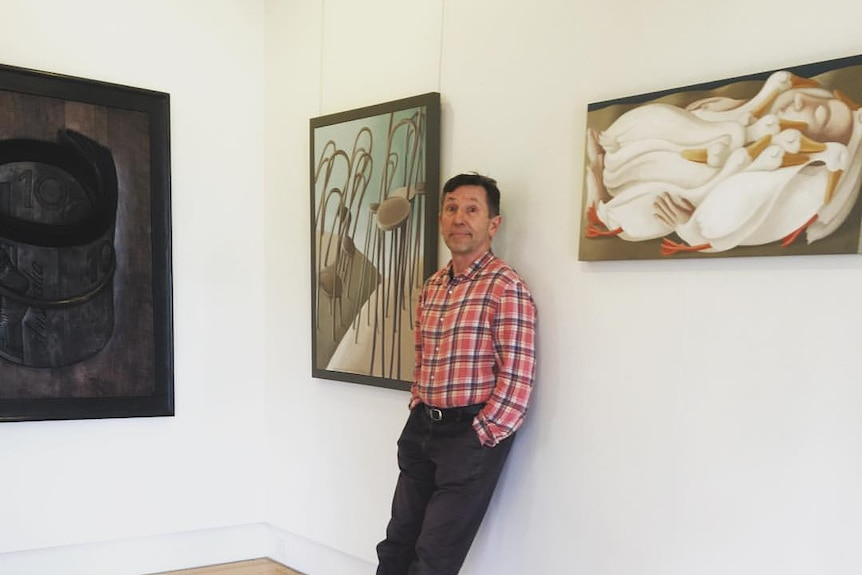 A man leans against a wall between two paintings