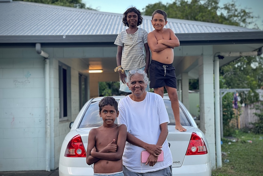 An older woman and three children stand around a car in front of a famiy home.