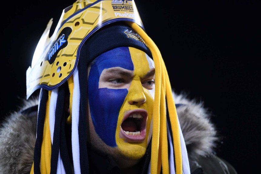 a fan in yellow, white and blue face paint with brumbies headwear and his mouth open