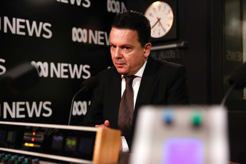 Concerned looking Nick Xenophon sitting in ABC Radio studio