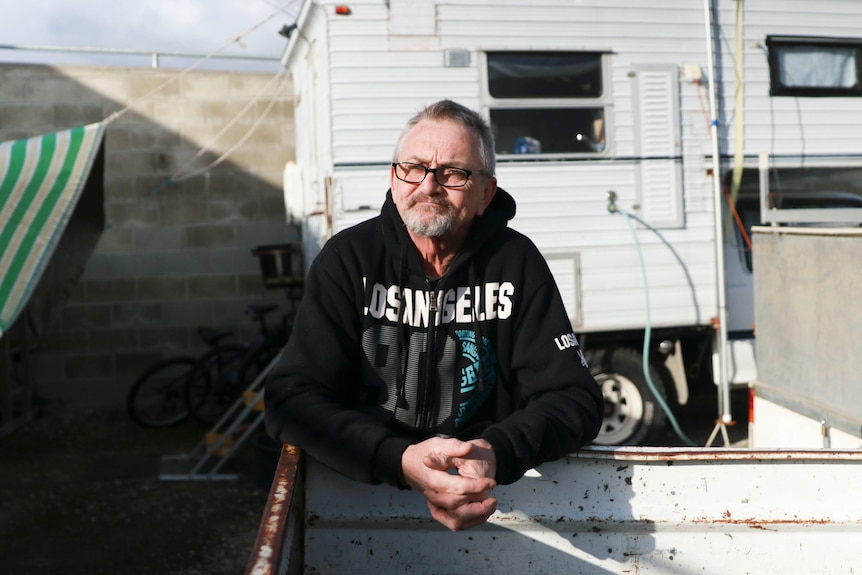 A man leans on a trailer with a campervan behind him.