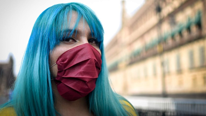 A woman with blue hair and a maroon face mask looks straight at the camera