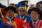 Robert Mugabe wears a blue and yellow graduation gown and walks in a crowd