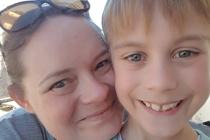 A close up of a woman's face and with a young boy. Both are smiling.