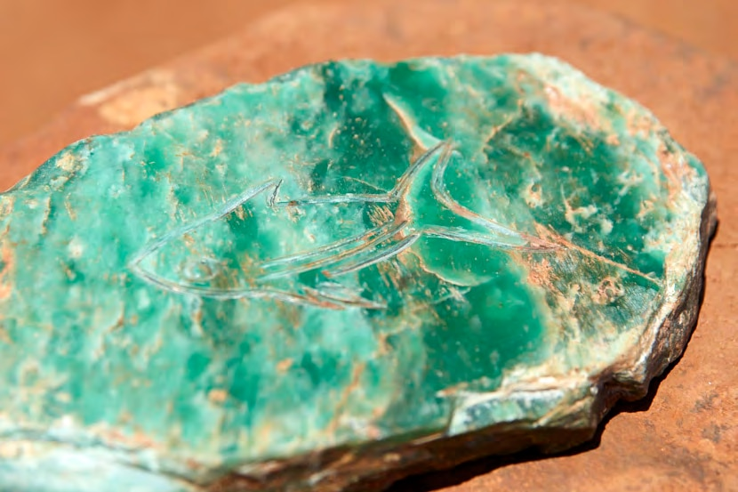 A weathered jade coloured flat stone with simple outline engraving of shark lies on red desert ground on sunny day.