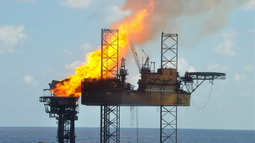 Flames from the burning Montara wellhead platform are blown on to the upper superstructure of the West Atlas rig.