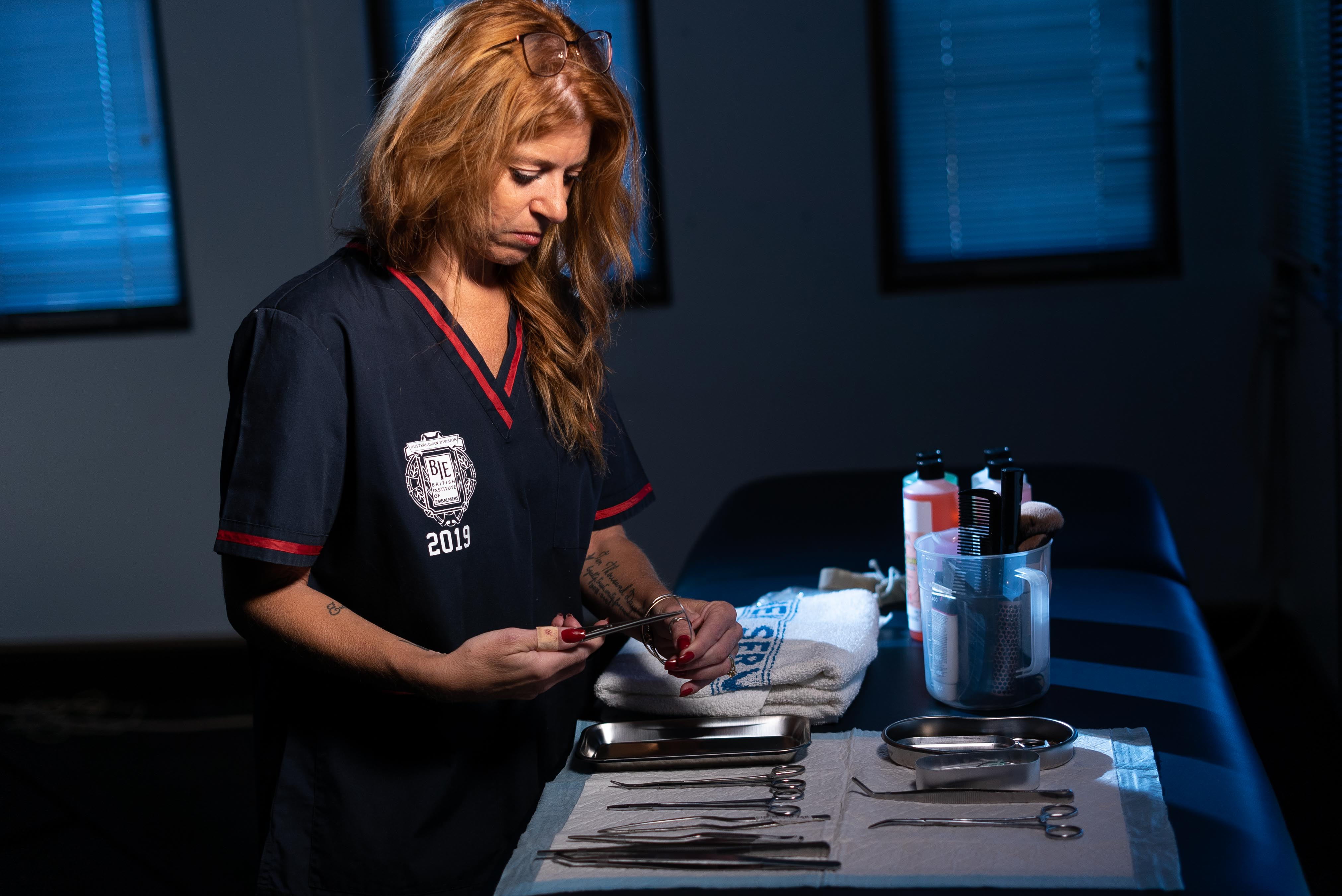 A woman in red hair handles surgical equipment in a dimly lit room