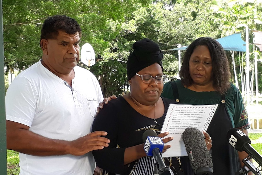 Family stand in front of microphones while reading a statement.