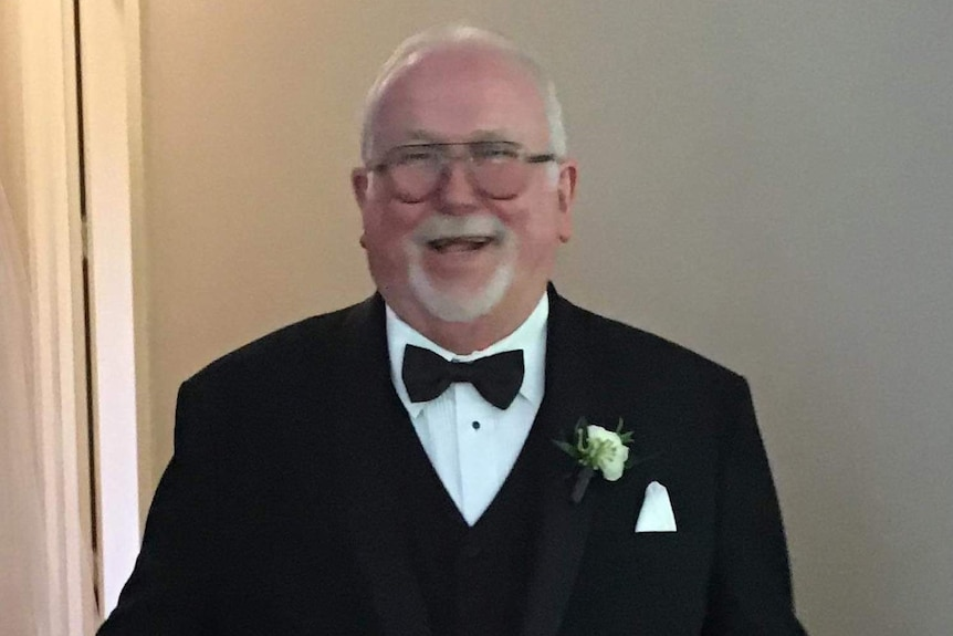 A mid shot of Tony Hickey laughing and smiling wearing a black tuxedo and bowtie.