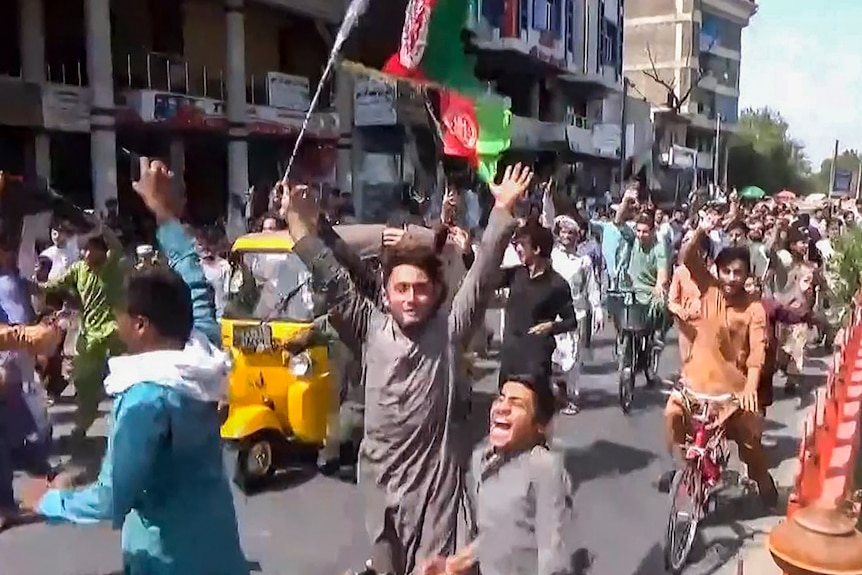 People holding the Afghanistan flag running on the street