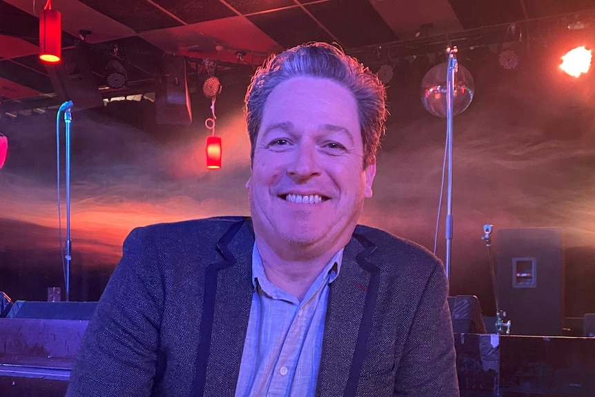 A smiling man wearing a jacket and open necked shirt smiles in a club.