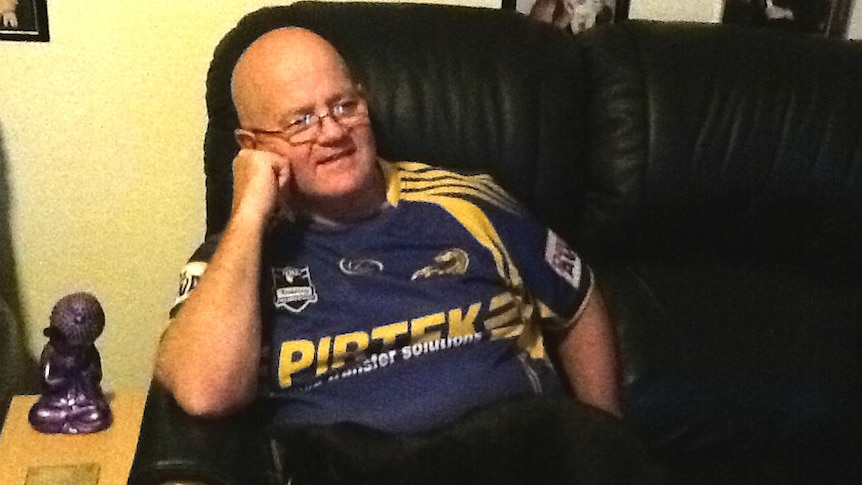 A man in a Parramatta Eels shirt sits on a couch