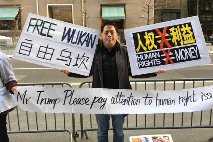 "A man holds up signs on the road ""Free Wukan"" and ""Trump please pay attention to human right issues"""