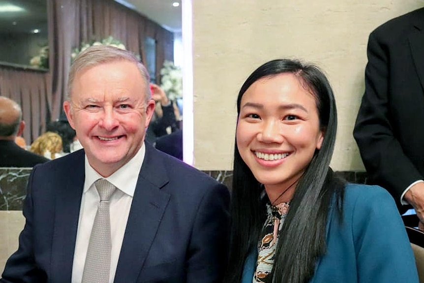 An older white man and a young Asian woman smile for the camera.