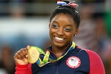 Simone Biles smiles as she holds a gold medal won at Rio 2016.