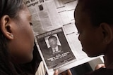 Two women looking at a newspaper add that shows a wanted picture of Felicien Kabuga.