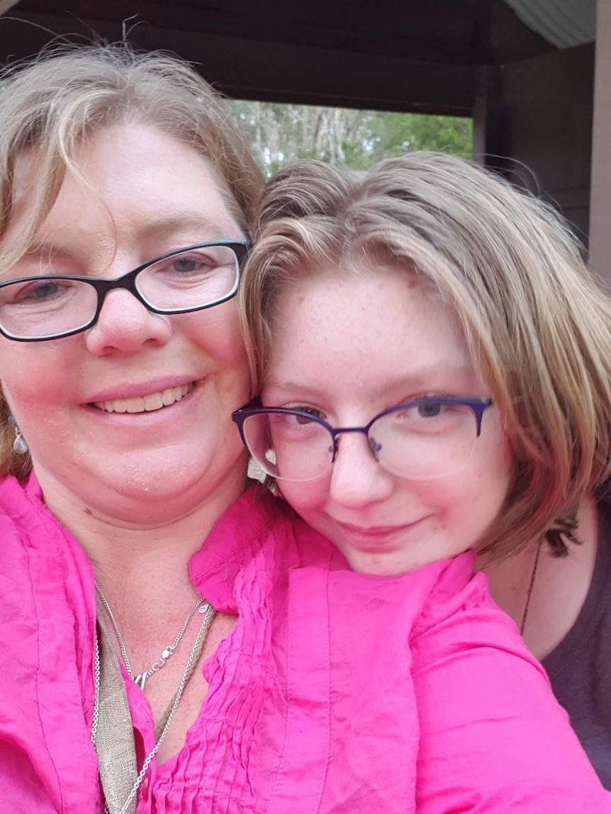 A woman is hugged by her daughter, both wearing glasses, in a selfie style photo