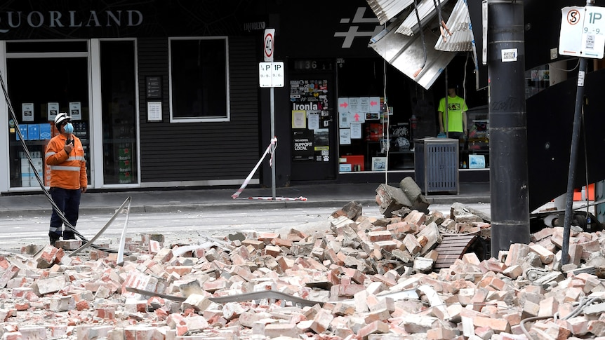 A person in high vis looks at building with bricks scattered on the ground.