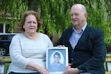 A man and a woman sit on a park bench holding a photo.