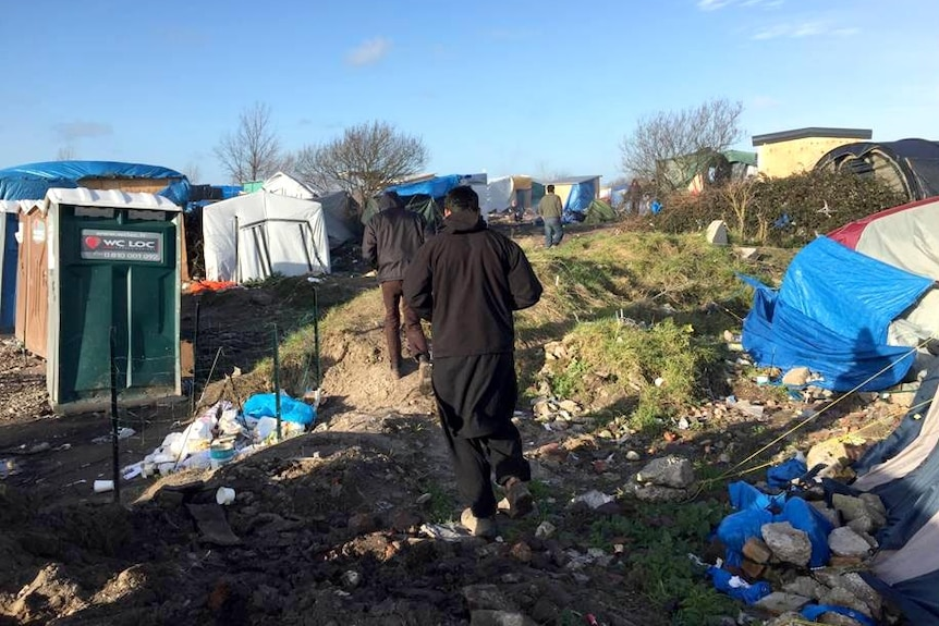 Refugees walk through the refugee camp, surrounded by tents and rubbish on the ground.