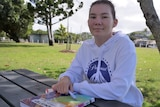 Chelsea Ajisaka, dark eyes and brown hair sits at a park table with her arms folded on top of her chemistry textbook.