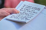 The hand of Donald Trump holds a notepad with notes written in thick black texta, which reads 'I want nothing' twice.