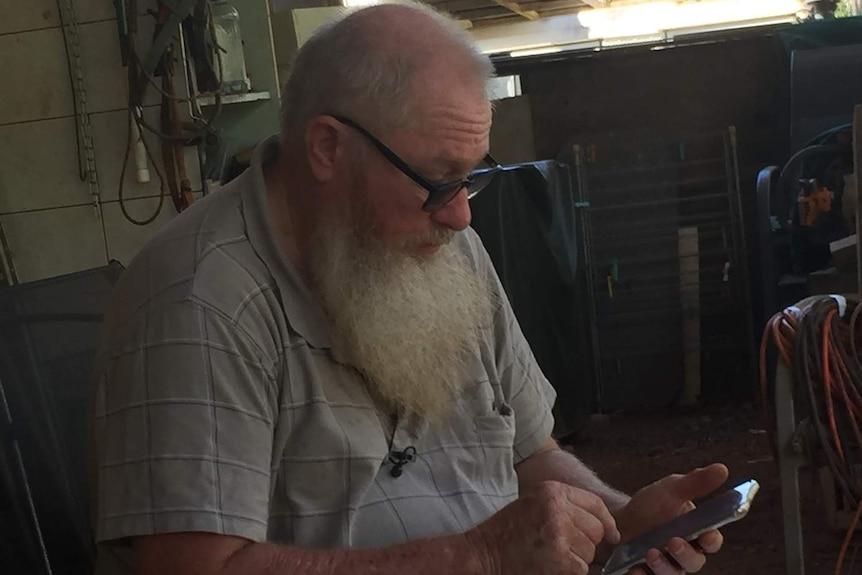Neil McDonald uses his mobile phone