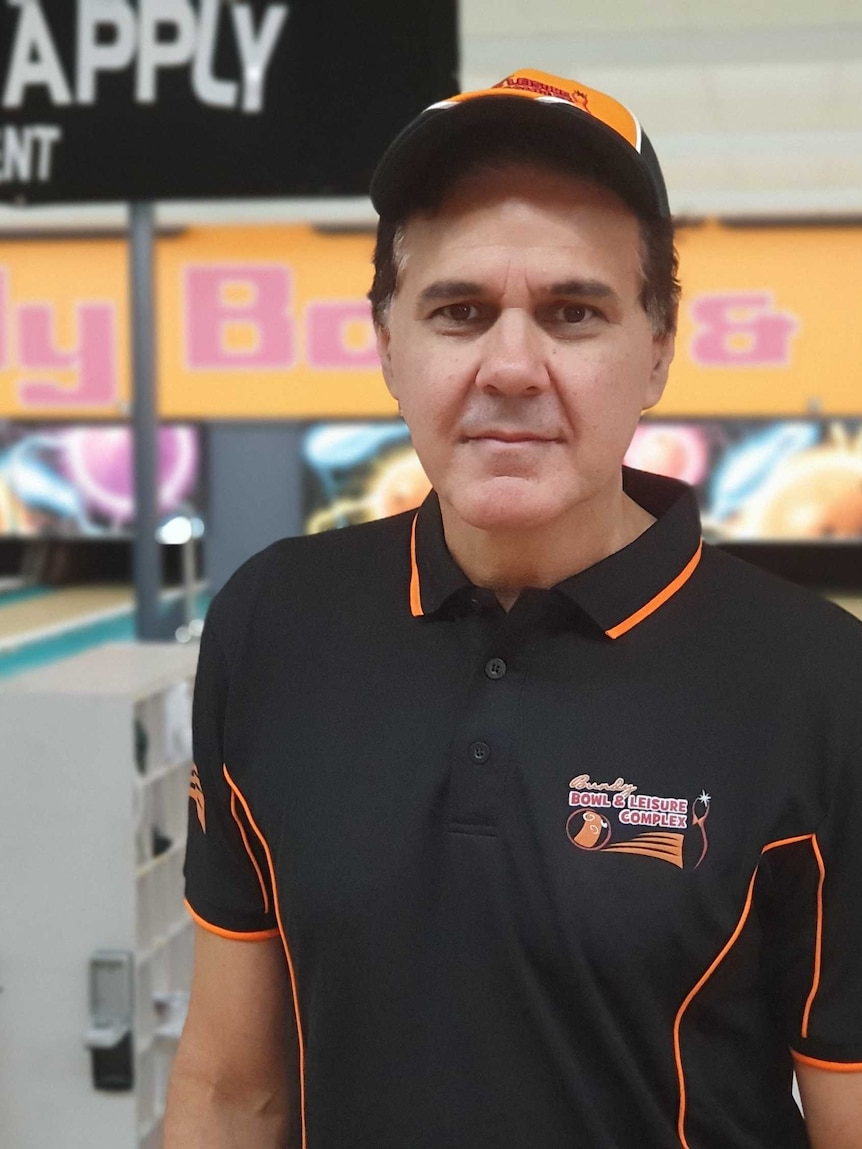 A man in a black and orange uniform stands in front of a bowling alley.