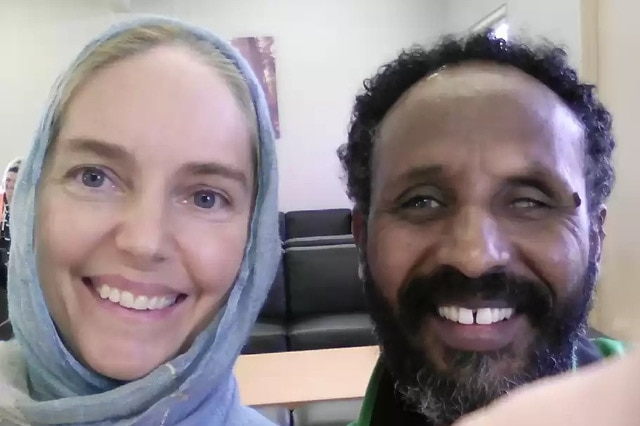 A picture of a white woman with blue eyes and a headscarf next to a Somali man smiling. He appears to have a cataract on one eye