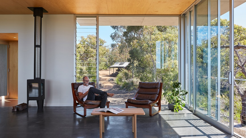Man sits in chair house with floor to ceiling windows, light flooding in from surrounding bushland