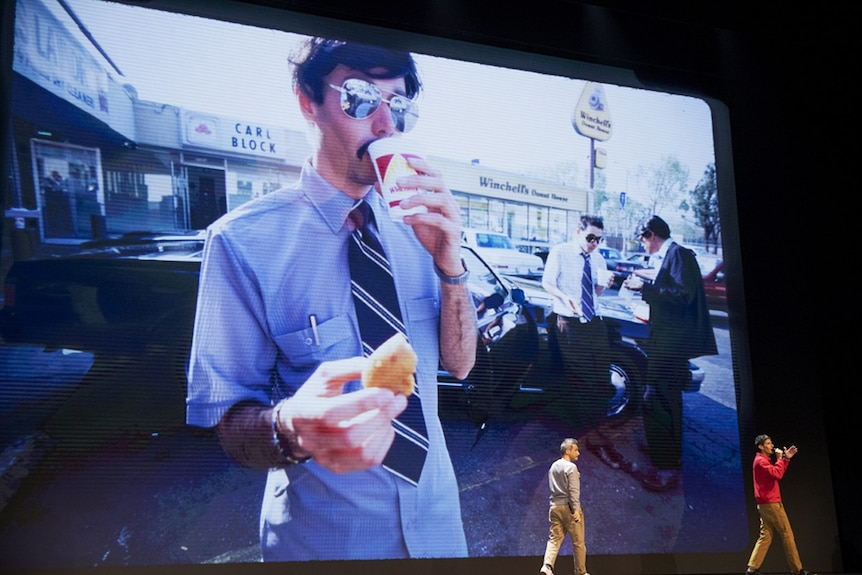 Two men on stage in front of large screen with photo of moustached man wearing sunglasses and eating and drinking in parking lot