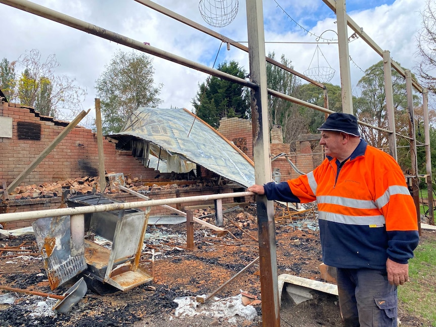 A man leaning on a steel frame looking at a pile of bricks and steel that was his house before it was hit by bushfire.